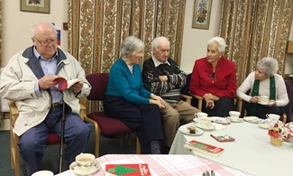 Elderly folk enjoying a Christmas treat with carols at Tea and Chat